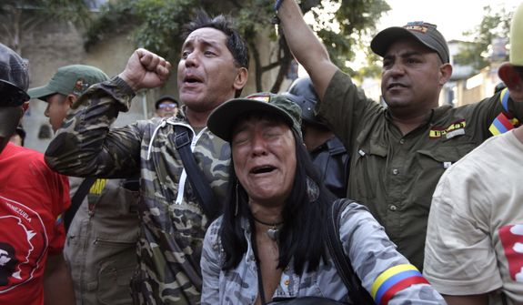 Supporters of Venezuela's President Hugo Chavez react as they learn that Chavez has died through an announcement by the vice president in Caracas, Venezuela, Tuesday, March 5, 2013. Venezuela's Vice President Nicolas Maduro announced that Chavez died on Tuesday at age 58 after a nearly two-year bout with cancer. During more than 14 years in office, Chavez routinely challenged the status quo at home and internationally. He polarized Venezuelans with his confrontational and domineering style, yet was also a masterful communicator and strategist who tapped into Venezuelan nationalism to win broad support, particularly among the poor. (AP Photo/Ariana Cubillos)