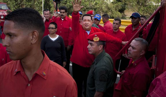 FILE - In this Aug. 3, 2012 file photo, Venezuela's President Hugo Chavez waves to supporters as he campaigns in the Antimano neighborhood of Caracas, Venezuela. Venezuela's Vice President Nicolas Maduro announced on Tuesday, March 5, 2013 that Chavez has died at age 58 after a nearly two-year bout with cancer. (AP Photo/Ariana Cubillos, File)