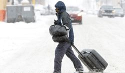 Maury Lawson drags his suitcase through the snow Monday, March 4, 2013, while crossing N.P. Avenue in Fargo, N.D., on his way to the bus depot. (AP Photo/Michael Vosburg, The Forum)
