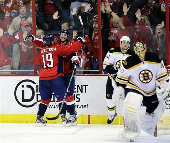 Washington Capitals right wing Eric Fehr, middle facing, celebrates his game-winning goal with center Nicklas Backstrom (19) as Boston Bruins goalie Tuukka Rask (40) skates off the ice in the overtime period of an NHL hockey