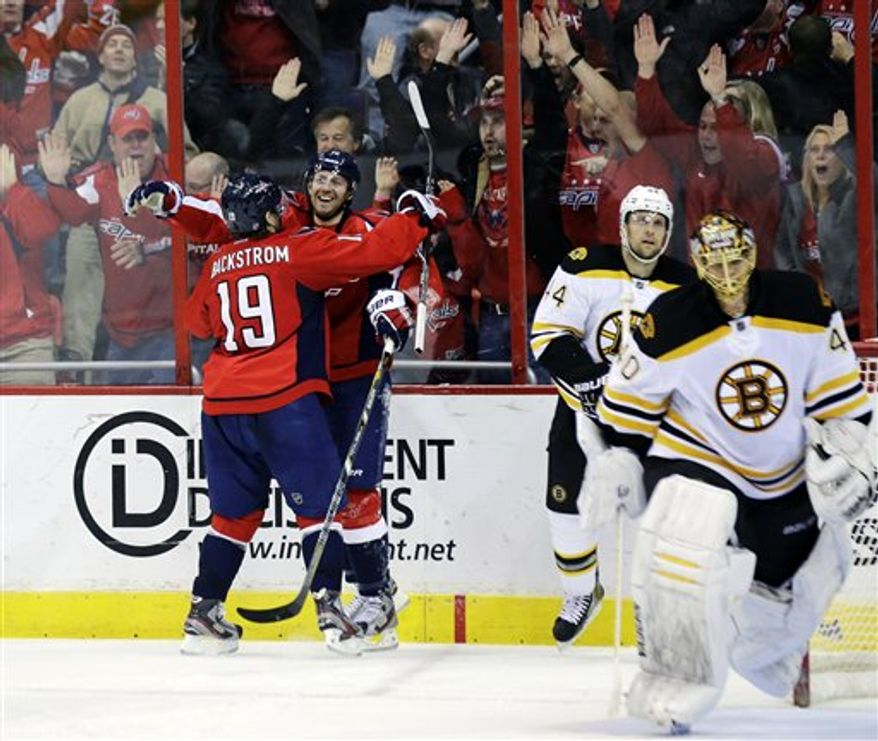 Washington Capitals right wing Eric Fehr, middle facing, celebrates his game-winning goal with center Nicklas Backstrom (19) as Boston Bruins goalie Tuukka Rask (40) skates off the ice in the overtime period of an NHL hockey game Tuesday, March 5, 2013 in Washington. The Capitals won 4-3. (AP Photo/Alex Brandon)