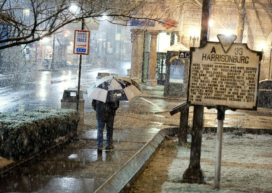James Madison University employee John Beach walks to work along Court Square in downtown Harrisonburg, Va., as snow begins to fall Tuesday night, March 5, 2013. (AP Photo/Daily News-Record, Michael Reilly)