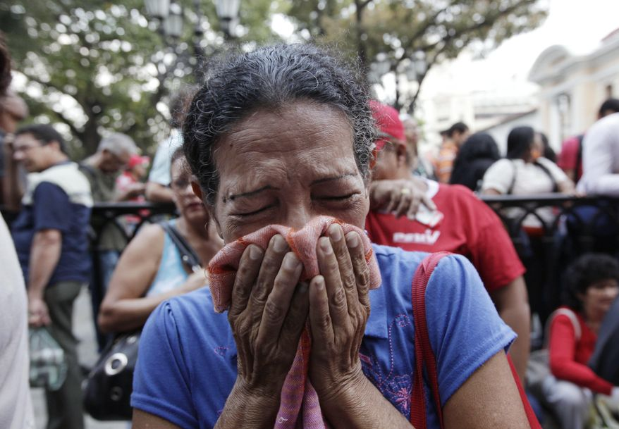A supporter of Venezuela's President Hugo Chavez cries as she learns that Chavez has died through an announcement by the vice president in Caracas, Venezuela, Tuesday, March 5, 2013. Venezuela's Vice President Nicolas Maduro announced that Chavez died on Tuesday at age 58 after a nearly two-year bout with cancer. (AP Photo/Ariana Cubillos)