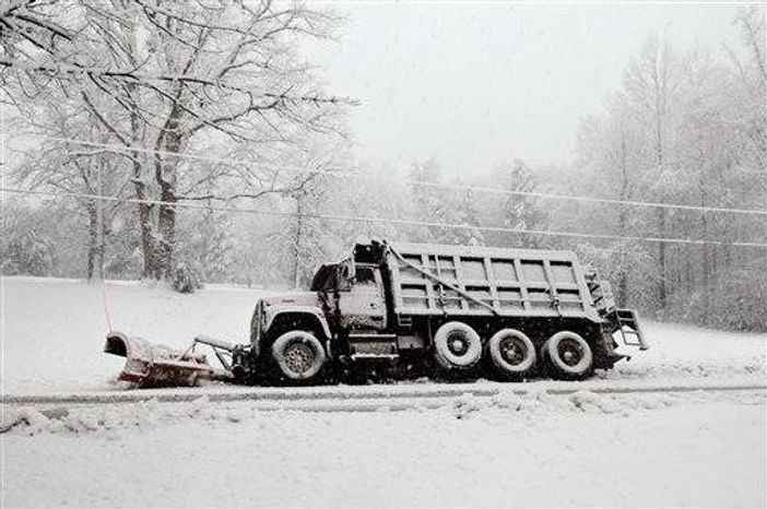 A snow plow rests in a ditch after sliding off of Brock Road in Spotsylvania,Va., Wednesday March 6, 2013. Gov. Bob McDonnell declared a state of emergency Wednesday as up to 20 inches of snow piled up in parts of central and western Virginia. (AP Photo/The Free Lance-Star,Dave Ellis )