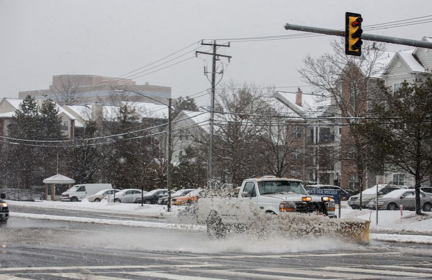 A truck uses its snowplow to remove slush from West Ox Road in Fairfax, Va., on March 6, 2013. (Andrew S. Geraci/The Washington Times)