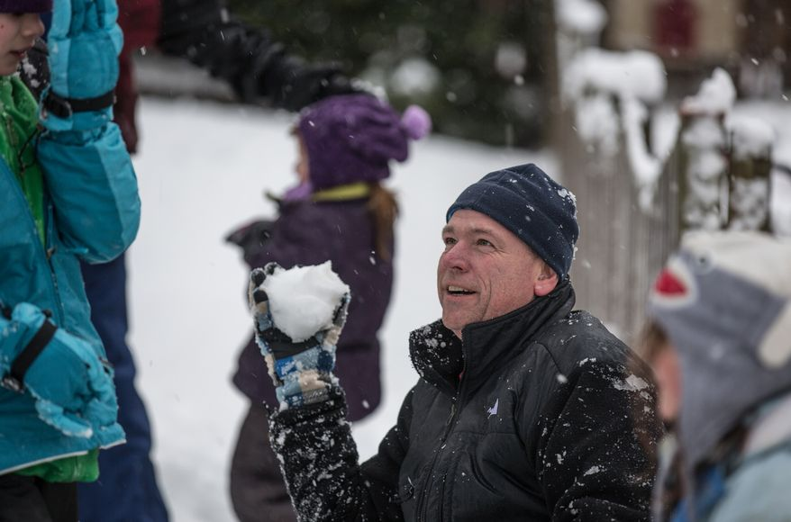 Patrick Sweeney prepares to throw a snowball at one of his children in Fairfax, Va., on March 6, 2013. (Andrew S. Geraci/The Washington Times)