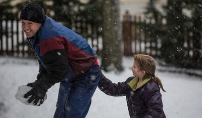 Mike Powers grimaces as his daughter drops snow down his pants during a snowball fight in Fairfax, Va., on March 6, 2013. (Andrew S. Geraci/The Washington Times)