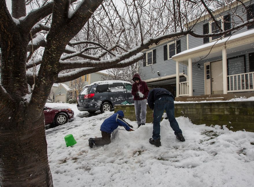 Mason Moy (center), 14, Sam Gustason (right), 13, and Calvin Crist, 13, build a snow fort in a front yard during a snow day in Fairfax, Va., on March 6, 2013. (Andrew S. Geraci/The Washington Times)