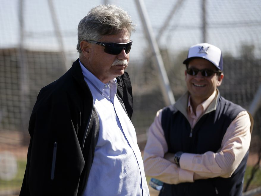 **FILE** Milwaukee Brewers general manager Doug Melvin talks to owner Mark Attanasio during a spring training baseball workout Saturday, Feb. 16, 2013, in Phoenix. (AP Photo/Morry Gash)