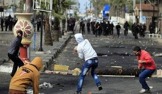 Egyptian protesters throw stones at riot police during clashes near a state security building in Port Said, Egypt, Thursday, March 7, 2013. Clashes between protesters and police continued into a fifth day on Thursday in the restive Egyptian city of Port Said. (AP Photo/Khalil Hamra)