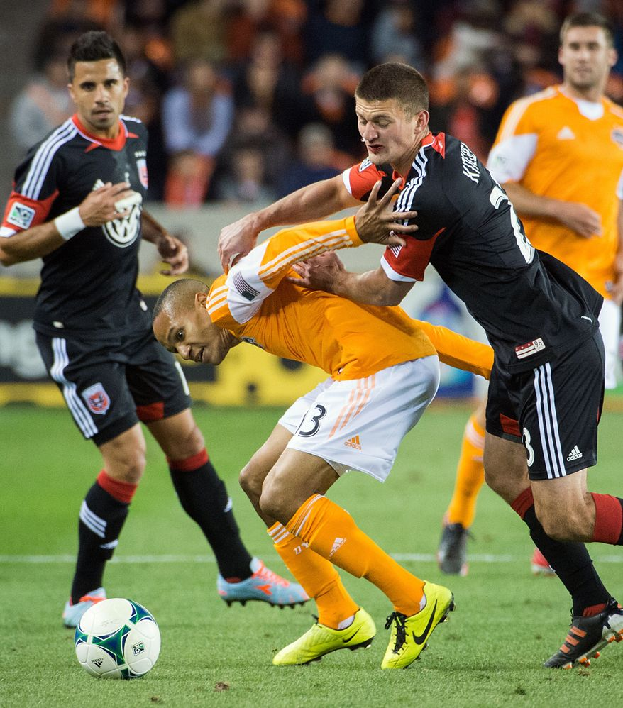 Houston Dynamo midfielder Ricardo Clark (13) tangles with D.C. United midfielder Perry Kitchen (23) during the first half of an MLS soccer match Saturday, March 2, 2013, in Houston. (AP Photo/Houston Chronicle, Smiley N. Pool)