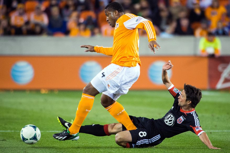 D.C. United midfielder John Thorrington (8) makes a sliding tackle against Houston Dynamo defender Jermaine Taylor (4) during the first half of an MLS soccer match Saturday, March 2, 2013, in Houston. (AP Photo/Houston Chronicle, Smiley N. Pool)