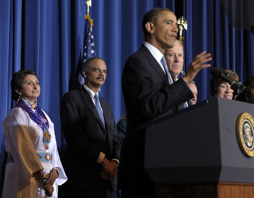 From left, Diane Millich, a member of the Southern Ute Indian Tribe in Colorado and domestic abuse survivor, Attorney General Eric Holder, Vice President Joseph R. Biden and Sen. Susan Collins, Maine Republican, listens to President Obama speaks at the Interior Department in Washington on March 7, 2013, before signing of the Violence Against Women Act. (Associated Press)