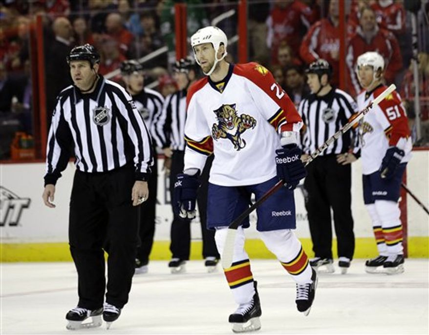 Linesman Michel Cormier (76) escorts Florida Panthers defenseman Tyson Strachan (23) out of the game after Strachan received a 5-minute game misconduct penalty in the second period of an NHL hockey game against the Washington Capitals Thursday, March 7, 2013 in Washington. (AP Photo/Alex Brandon)