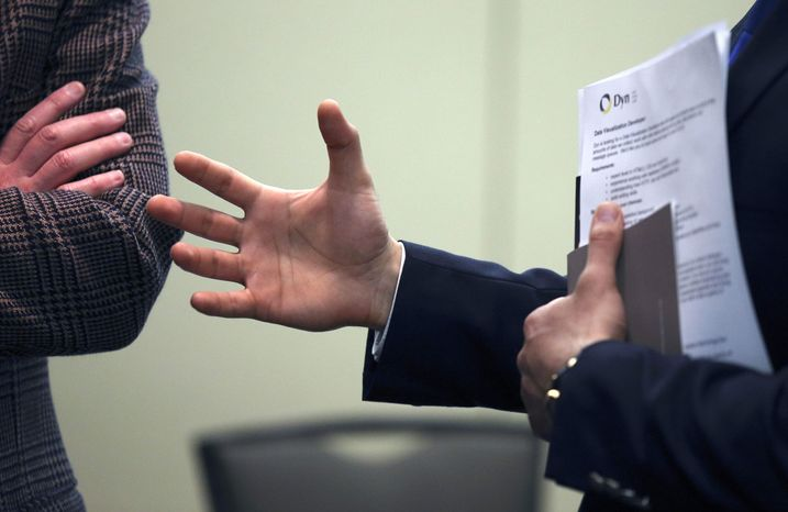 In this Monday, Feb. 25, 2013, photo, Sayed Mouawad, right, of Providence, R.I., gestures while speaking to a company representative during a job fair in Boston. U.S. employers ramped up hiring in February, adding 236,0