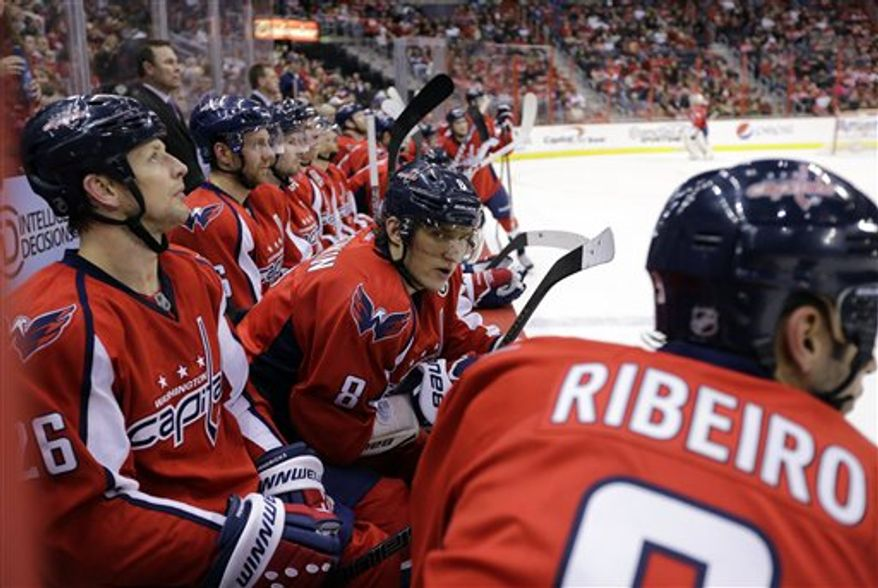 Washington Capitals center Matt Hendricks (26), left wing Alex Ovechkin (8), from Russia, and center Mike Ribeiro (9), and others, rest on the bench during a timeout in the third period of an NHL hockey game against the Florida PanthersThursday, March 7, 2013 in Washington. The Capitals won 7-1. (AP Photo/Alex Brandon)