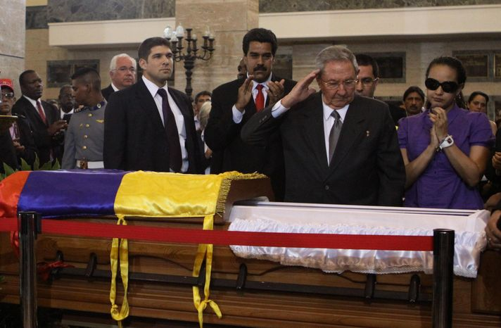 ** FILE ** In this photo released by Miraflores Press Office, Cuba's President Raul Castro salutes as he stands next to the coffin containing the body of Venezuela's late President Hugo Chavez during his wake at a military academy where his body will lie in state until his funeral in in state in Caracas, Venezuela, Thursday, March 7, 2013. (AP Photo/Miraflores Press Office)