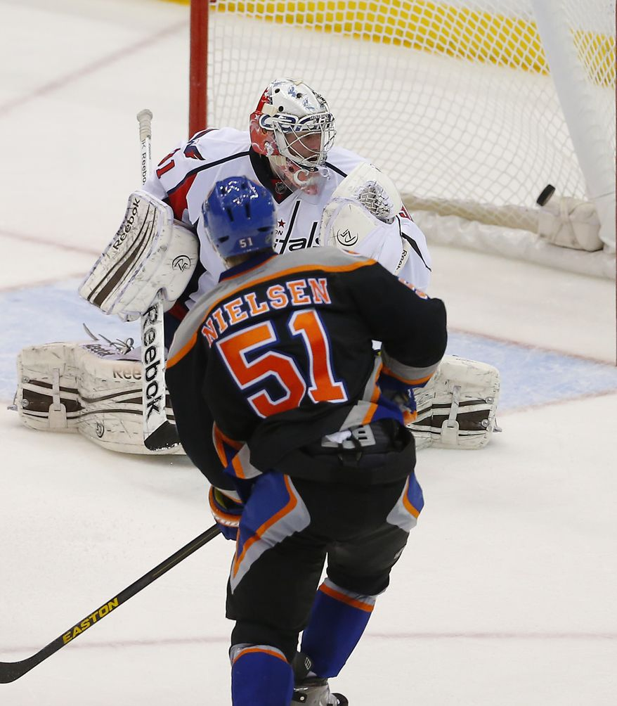 Washington Capitals goalie Philipp Grubauer (31) is beaten for a goal by New York Islanders center Frans Nielsen (51) during the third period of an NHL hockey game at the Nassau Coliseum in Uniondale, N.Y., Saturday, March 9, 2013. (AP Photo/Paul J. Bereswill)
