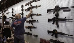 ** FILE ** Gun dealer Mel Bernstein takes down an AK-47 assault rifle from a sales rack at his own Dragonman's shooting range and gun store, east of Colorado Springs, Colo., Feb. 15. (AP Photo/Brennan Linsley)