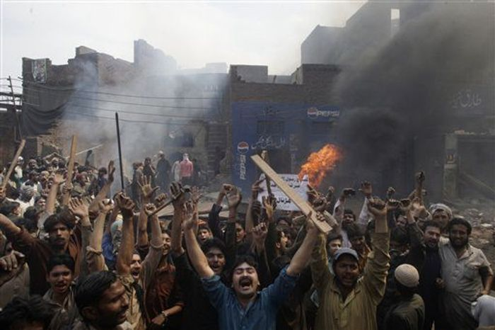 """An angry mob reacts after burning Christian houses in Lahore, Pakistan, Saturday, March 9, 2013. Hundreds of people in the eastern Pakistani city of Lahore attacked a Christian neighborhood Saturday and set fire to homes after hearing accusations that a Christian man had committed blasphemy against Islam's prophet Mohammed, said a police officer. Placard center reads, """" Blasphemer is liable to death."""" (AP Photo/K.M. Chaudary)"""