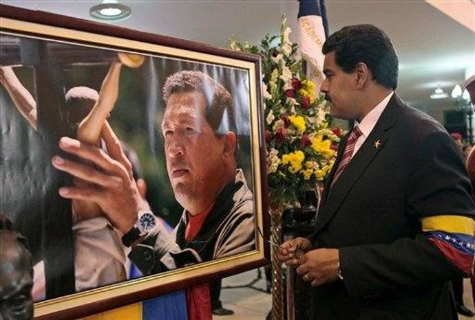 Venezuela's acting President Nicolas Maduro stands in front of a portrait of Venezuela's late President Hugo Chavez after a symbolic swearing in ceremony in the presence of the flag-draped coffin of Chavez at the military academy where the funeral ceremony was held earlier in Caracas, Venezuela, Friday, March 8, 2013. Chavez died on March 5 after a nearly two-year bout with cancer. (AP Photo/Miraflores Press Office)
