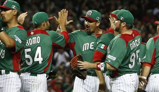 Mexico's Sergio Romo (54) gets a high-five from Adrian Gonzalez as they celebrate with teammates Karim Garcia (95), Luis Alfonso Garcia, and others after a World Baseball Classic baseball game against the United States on Friday, March 8, 2013, in Phoenix. Mexico defeated the United States 5-2. (AP Photo/Ross D. Franklin)