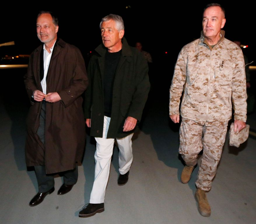 THE LATEST: Gen. Joseph F. Dunford, Jr., (right) takes the hand and the command of Gen. John Allen during a February ceremony in Kabul, Afghanistan. Gen. Dunford became the fifth commander of the war in the past five years. (Associated Press)
