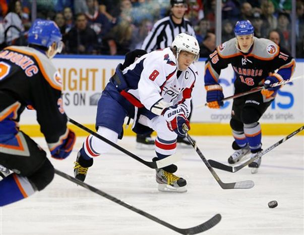 Washington Capitals left wing Alex Ovechkin (8) moves the puck in front of New York Islanders defenseman Travis Hamonic (3) and Marty Reasoner (16) during the third period of an NHL hockey game at the Nassau Coliseum in Uniondale, N.Y., Saturday, March 9, 2013. The Islanders won 5-3.(AP Photo/Paul J. Bereswill)