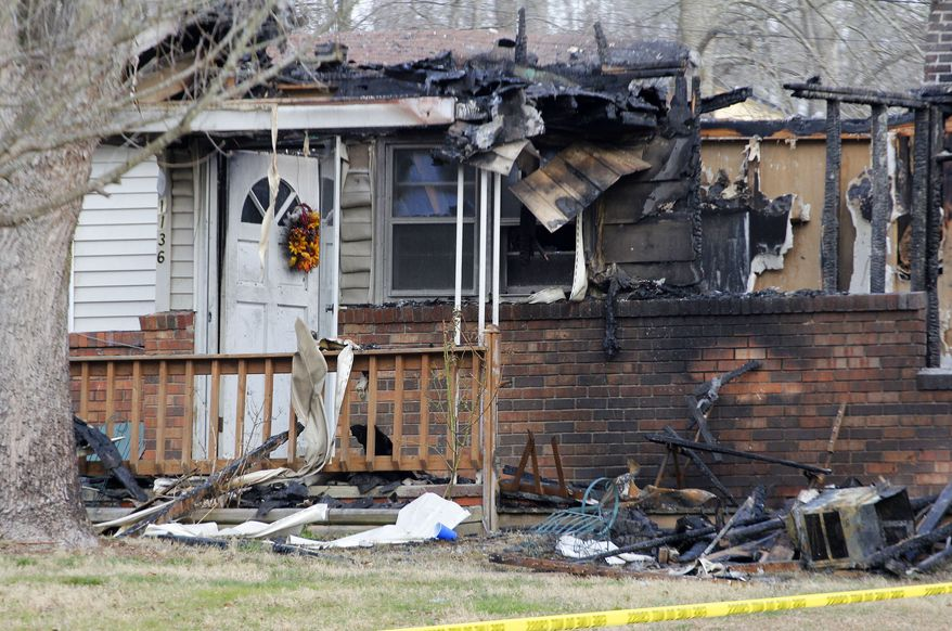 The charred remains of a home in Gray, Ky., are pictured on Sunday, March 10, 2013, after a fire erupted Saturday and killed two adults and five children inside. (AP Photo/Lisa Norman-Hudson)