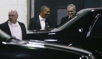 President Obama (center) and White House Chief of Staff Denis McDonough (right) leave the annual Gridiron Dinner through a loading area at the Renaissance Hotel in Washington on Saturday, March 9, 2013. (AP Photo/Charles Dharapak)