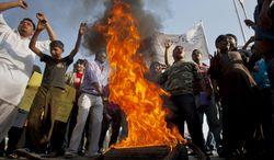 Pakistani Christians chant slogans as they burn a tire during a demonstration demanding that the government rebuild their homes after they were burned down following an alleged blasphemy incident, in Islamabad on Sunday, March 10, 2013. (AP Photo/Anjum Naveed)