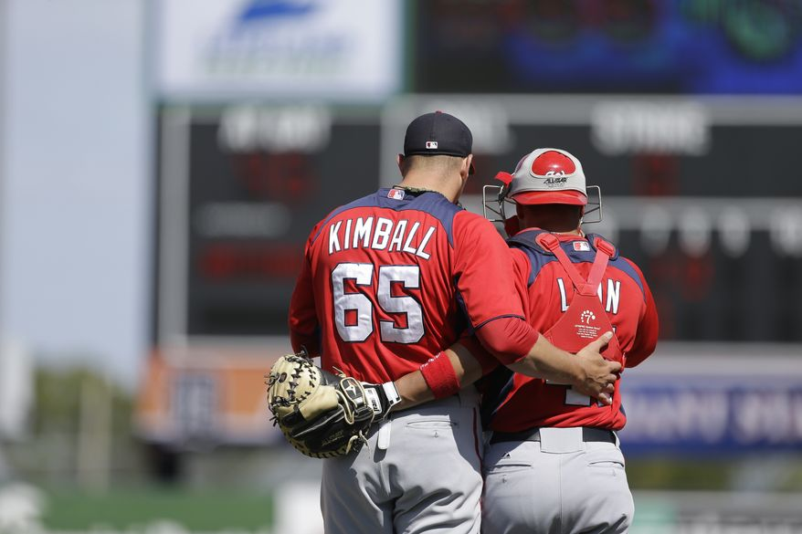 Washington Nationals relief pitcher Cole Kimball (65) and catcher Sandy Leon (41) talk during the eighth inning of an exhibition spring training baseball game against the Detroit Tigers, Sunday, March 10, 2013 in Lakeland, Fla. (AP Photo/Carlos Osorio)