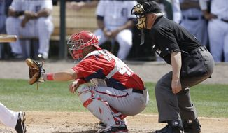 Washington Nationals catcher Wilson Ramos and homeplate umpire Larry Vanover are seen during the fifth inning of an exhibition spring training baseball game against the Detroit Tigers, Sunday, March 10, 2013 in Lakeland, Fla. (AP Photo/Carlos Osorio)