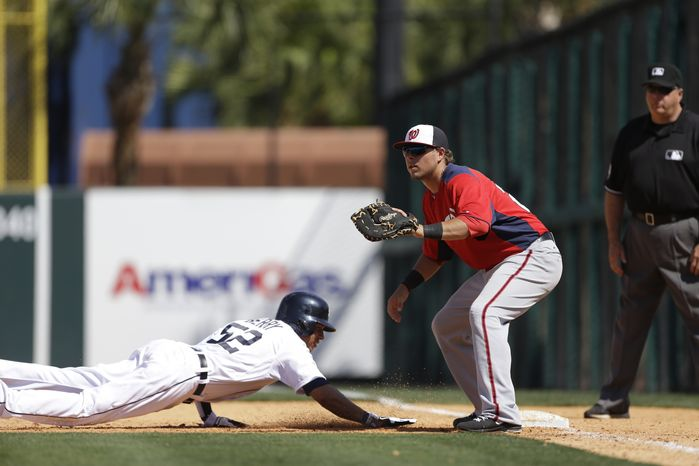 Detroit Tigers' Quintin Berry jumps back to first as Washington Nationals first baseman Matt Skole waits for the throw during the seventh inning of an exhibition spring training baseball game, Sunday, March 10, 2013 in Lakeland, Fla. (AP Photo/Carlos Osorio)