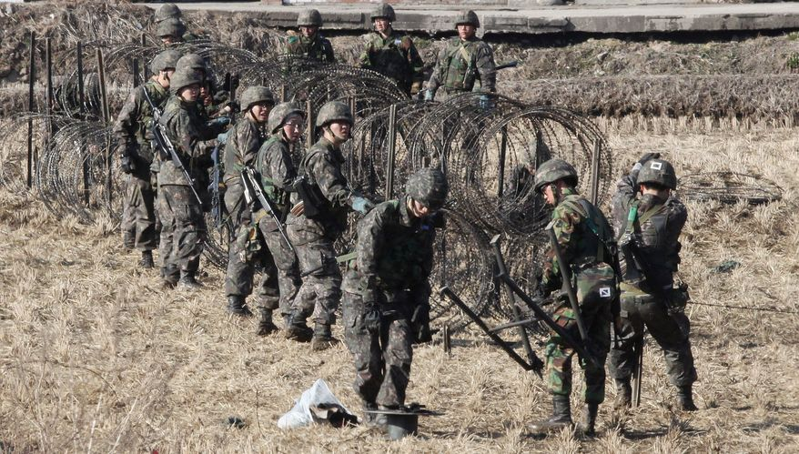 South Korean Army soldiers set up barbed wire fence during an exercise against possible attacks by North Korea near the border village of Panmunjom in Paju, South Korea, Monday, March 11, 2013. (AP Photo/Ahn Young-joon)