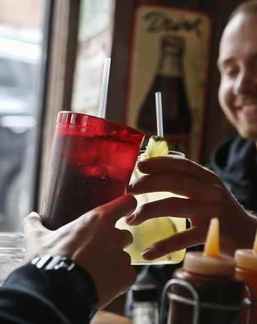 **FILE** Customers at Brother Jimmy's BBQ in New York call cheers with 24-ounce (left) and 16-ounce beverages on March 8, 2013. (Associated Press)