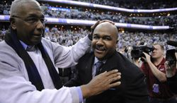 John Thompson Jr., left, congratulates his son Georgetown head coach John Thompson III, right, after an NCAA college basketball game against Syracuse, Saturday, March 9, 2013, in Washington. Georgetown won 61-39 over Syracuse. (AP Photo/Nick Wass) **FILE**