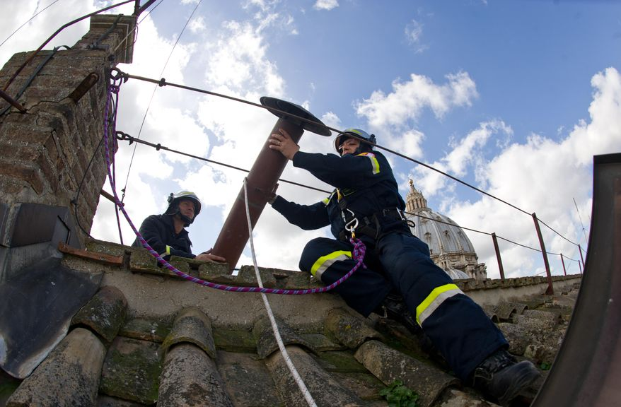 Firefighters install the top of the Sistine Chapel chimney at the Vatican on Saturday, March 9, 2013. Smoke from the chimney during the conclave of cardinals will signal whether or not a new pope has been elected. (AP Photo/L'Osservatore Romano)