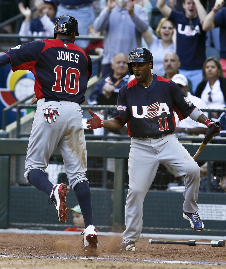United States' Adam Jones (10) celebrates his run scored against Canada with teammate Jimmy Rollins (11) in the eighth inning of a World Baseball Classic baseball game on Sunday, March 10, 2013, in Phoenix. The United States defeated Canada 9-4. (AP Photo/Ross D. Franklin)