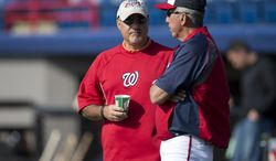 Washington National GM Mike Rizzo, left, talks with manager Davey Johnson before the start of an exhibition spring training baseball game on Monday, March 11, 2013, in Viera, Fla. (AP Photo/Evan Vucci)