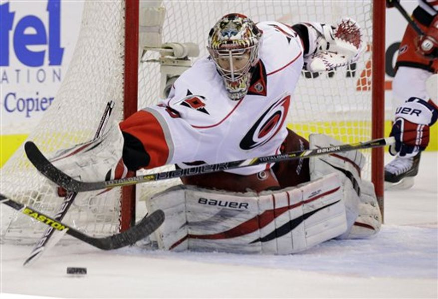 Carolina Hurricanes goalie Justin Peters (35) reaches for the puck in the second period of an NHL hockey game against the Washington Capitals on Tuesday, March 12, 2013, in Washington. (AP Photo/Alex Brandon)