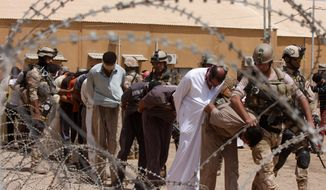 ** FILE ** In this Friday, July 20, 2012, file photo, blindfolded and handcuffed suspected al Qaeda members are led away to detention centers in an Iraqi army base in Hillah, Iraq. (AP Photo/ Alaa al-Marjani, File)