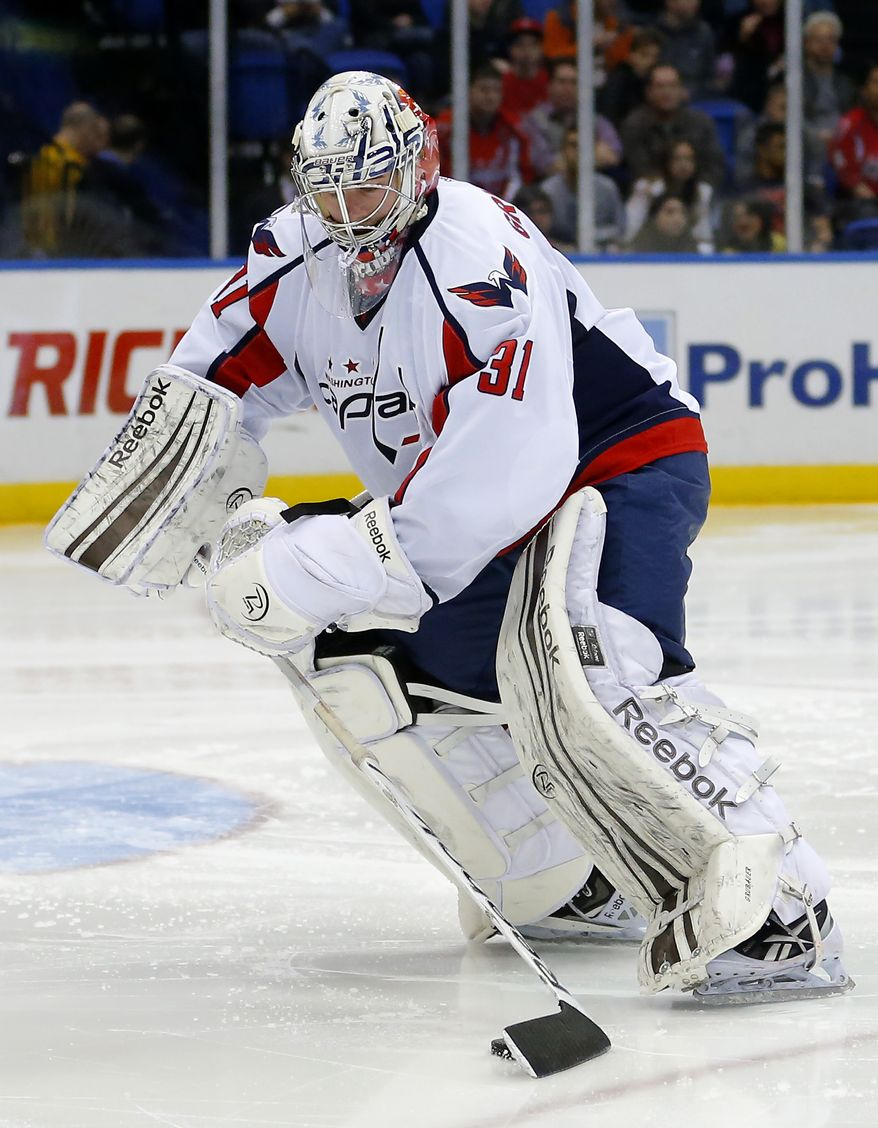 Washington Capitals goalie Philipp Grubauer (31) clears the puck in an NHL hockey game against the New York Islanders at the Nassau Coliseum in Uniondale, N.Y., Saturday, March 9, 2013. (AP Photo/Paul J. Bereswill)