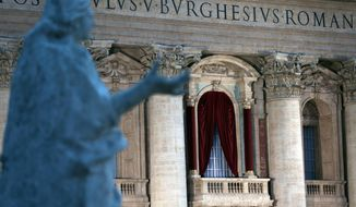 A floodlight illuminates the central balcony of St. Peter's Basilica, from where the newly elected pope will salute the crowd, at the Vatican, Tuesday, March 12, 2013. (AP Photo/Luca Bruno)