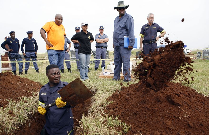 A South African Police Service forensic officer digs up a grave for the exhumation of two bodies that are believed to be those of young activists at Avalon Cemetery in Johannesburg on Tuesday, March 12, 2013. Authorities believe the bodies are those of two young activists last seen 24 years ago at the home of Winnie Madikizela-Mandela. (AP Photo/Themba Hadebe)