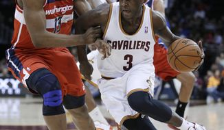 Cleveland Cavaliers' Dion Waiters (3) drives to the basket against Washington Wizards' Kevin Seraphin (13), from France, during the second quarter of an NBA basketball game Tuesday, March 12, 2013, in Cleveland. (AP Photo/Tony Dejak)