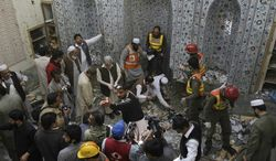 Pakistani security officials and rescue workers examine the site of bomb blast inside a mosque in Peshawar, Pakistan, on Saturday, March 9, 2013. (AP Photo/Mohammad Sajjad)