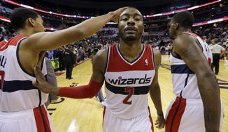 Washington Wizards guard John Wall, center, celebrates with guard Garrett Temple, left, and forward Martell Webster after an NBA basketball game against the Milwaukee Bucks, Wednesday, March 13, 2013, in Washington. The Wizards won 106-93. (AP Photo/Alex Brandon)
