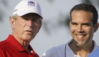 **FILE** George P. Bush (right) stands with his uncle, former President George W. Bush, during a charity golf tournament in Irving, Texas, in 2012. (Associated Press)