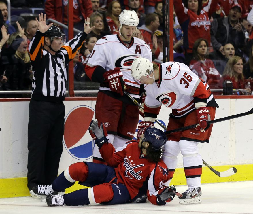 Washington Capitals center Mathieu Perreault (85), pleads his case to referee Greg Kimmerly (18) with Carolina Hurricanes center Jordan Staal (11) and left wing Jussi Jokinen (36), from Finland, nearby, in the second period of an NHL hockey game Tuesday, March 12, 2013 in Washington. (AP Photo/Alex Brandon)